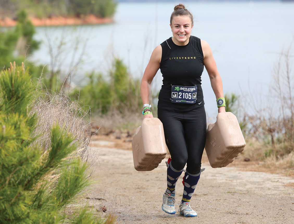 Madison Levy hauls weighted containers during an obstacle.