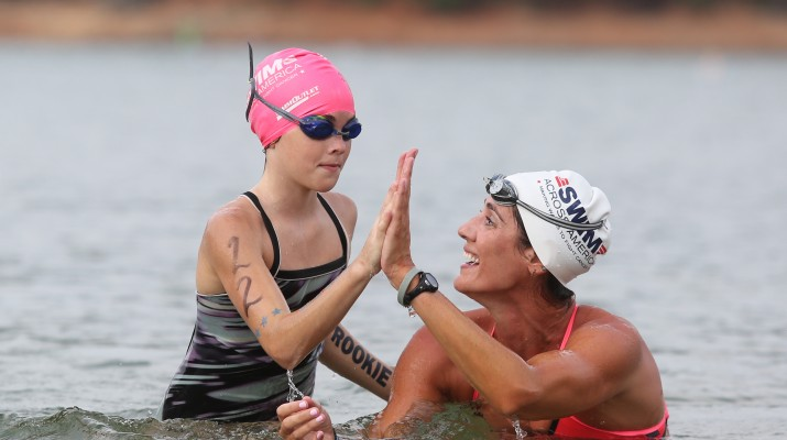 Olympians Kristy Kowal gives a swimmer a high five during Swim Across America.