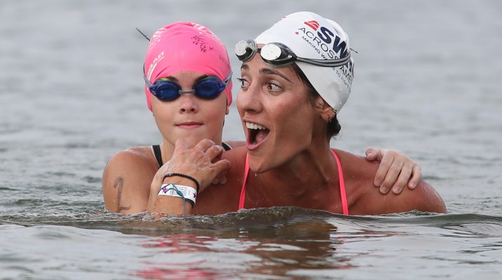 Olympians Kristy Kowal carries a young swimmer on her back during Swim Across America.