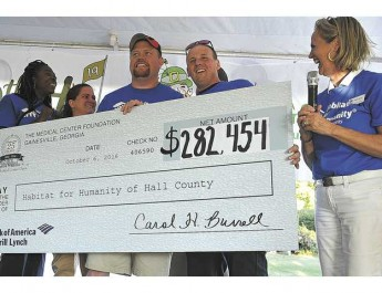 Habitat for Humanity of Hall County Executive Director Ann Nixon, right, announces the recipients of the next three homes to be built Thursday afternoon at Chicopee Woods Golf Course during the annual  Medical Center Open fundraiser. New home owners are from the left, Meoshea Columbus, Holly and Joseph Byrd, and Caleb Last.