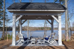A pavilion has a fire pit, heating fixtures and a ceiling fan keeps things comfortable.
